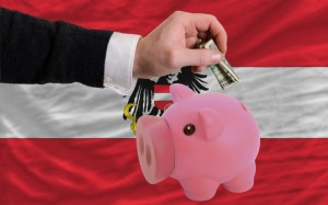 Man putting dollar into piggy rich bank national flag of austria in foreign currency because of inflation